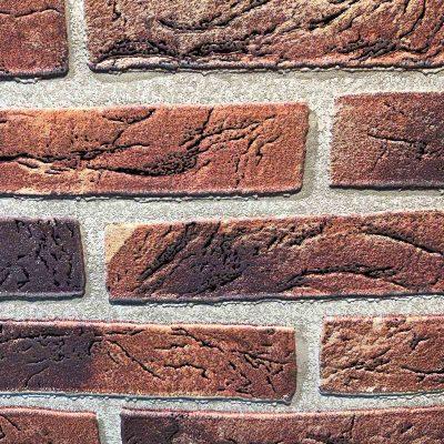 Rød murstenstapet i en tyk skumvinyl. Den er præget så man kan mærke murstenene. Klisteren påføres på rullen