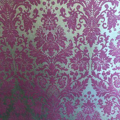 Guldtapet med mørk pinkfarvet blomstermønster. Opsættes ved at rulle lim på væggen. Ophøjet mønster